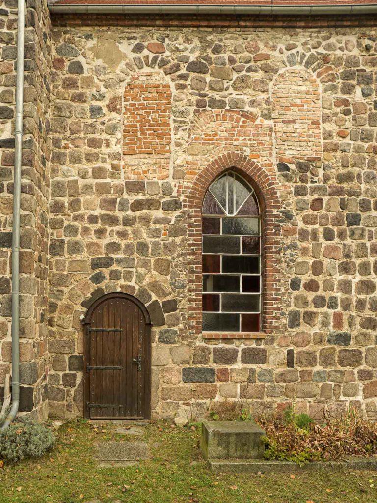 Dorfkirche Hönow. Originale Priesterpforte und Rundbogenfenster in der Südwand des Chors.