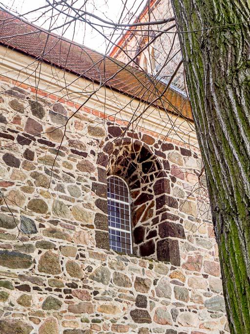 Originales, mit Raseneisenstein verkleidetes Rundbogenfenster in der Nordwand des Schiffes