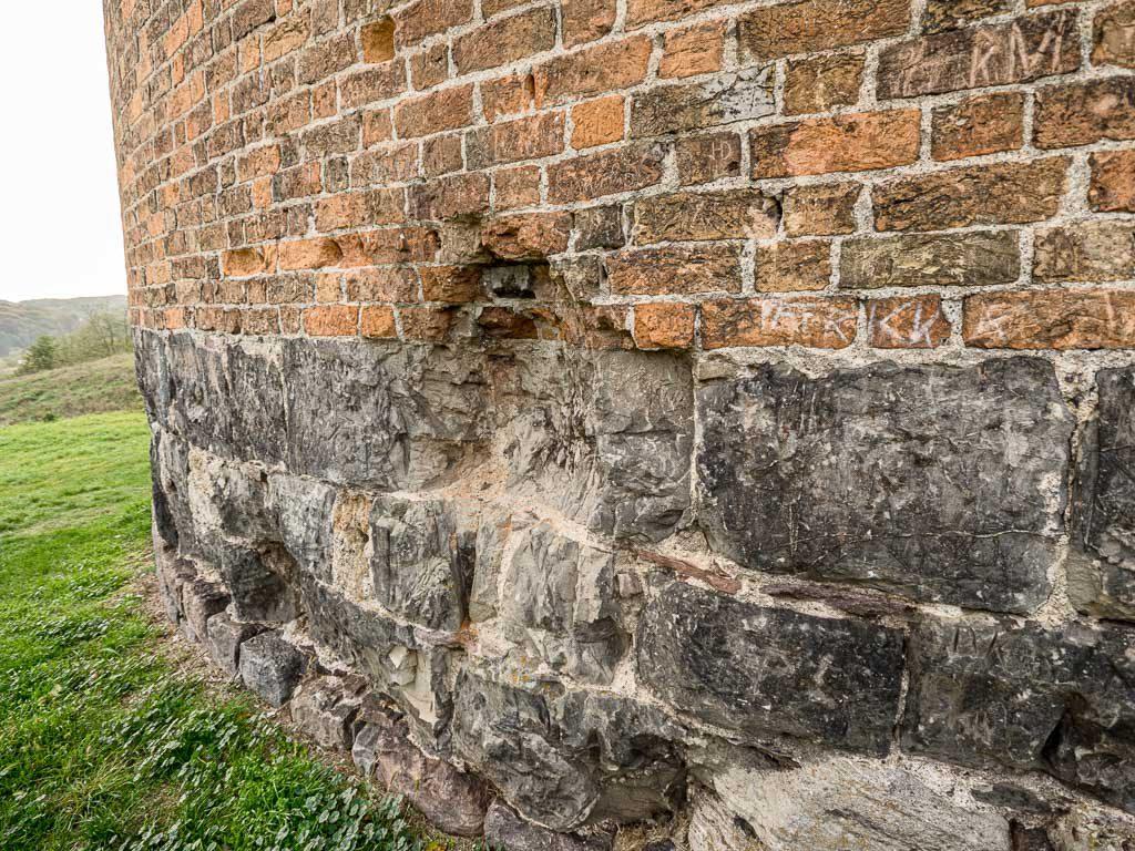 Burg Stolpe Direkt über dem Bodenniveau sind behauener Feldsteine erkennbar, darüber drei Lagen behauener Höör-Sandsteine. In der Bildmitte sieht man eine Kriegsbeschädigung.