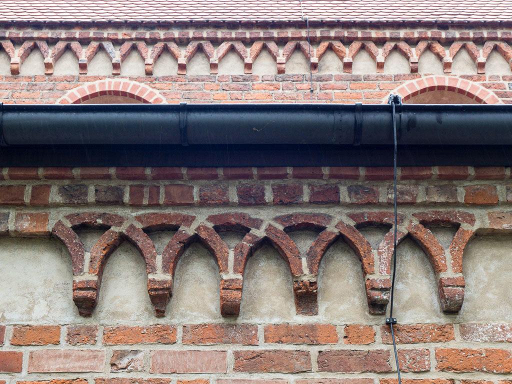 Romanisches Kreuzbogenfries (unten) am südlichen Seitenschiff und Spitzbogenfries.