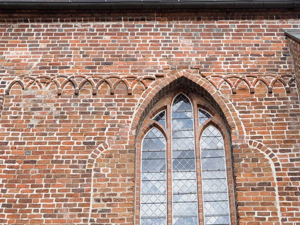 Stadtkirche Rathenow Kreuzbogenfries durchbrochen von gotischem Fenster