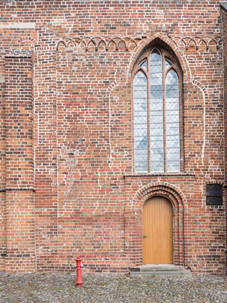 Stadtkirche Rathenow. Romanische Reste in der Südfassade des Schiffs. Gemeindepforte, Kreuzbogenfries und zugesetztes Rundbogenfenster.