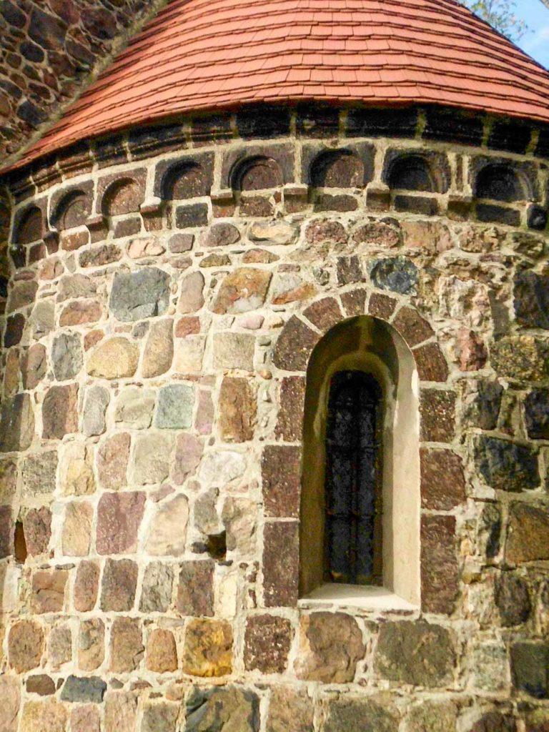 Rundbogenfries aus Raseneisenstein und Mörtel. Fasche des Fensters abgesetzt mit Raseneisenstein. Dorfkirche Riedebeck.
