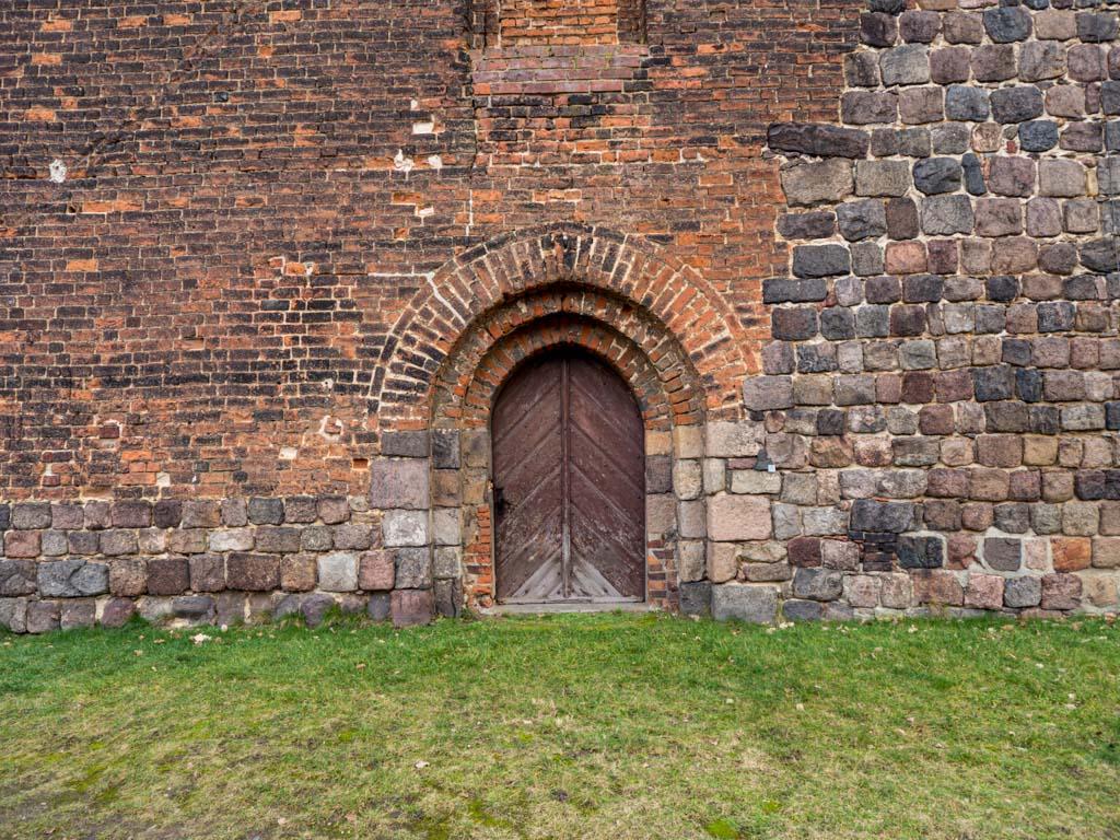 Stadtkirche Zahna-Elster. Westportal und untere Westfassade, begonnen in Feldstein, fertiggestellt in Backstein. Portal mit Begleitbogen.