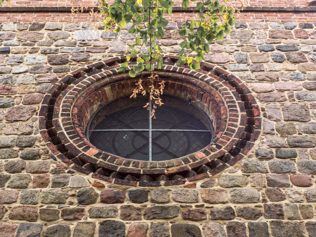 Rundfenster mit Zahnfries. Backstein dient der Ornamentierung einer Feldsteinfassade. Liebfrauenkirche Jüterbog.