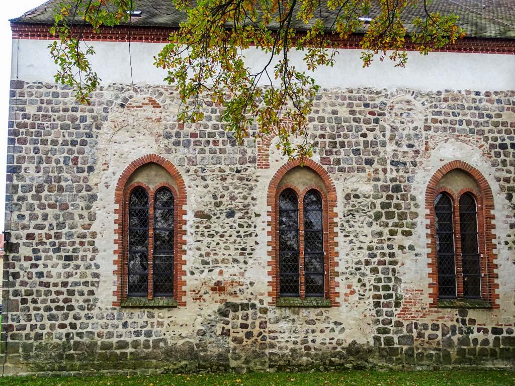 Nordfassade des Chors. Drei Generationen von Fenstern sind erkennbar. Ganz oben im Bild die jetzt zugesetzten originalen, romanischen. Unten in der Mitte ist die zugesetzte Priesterpforte zu sehen, rechts eine zugesetzte Öffnung unbekannter Bestimmung.