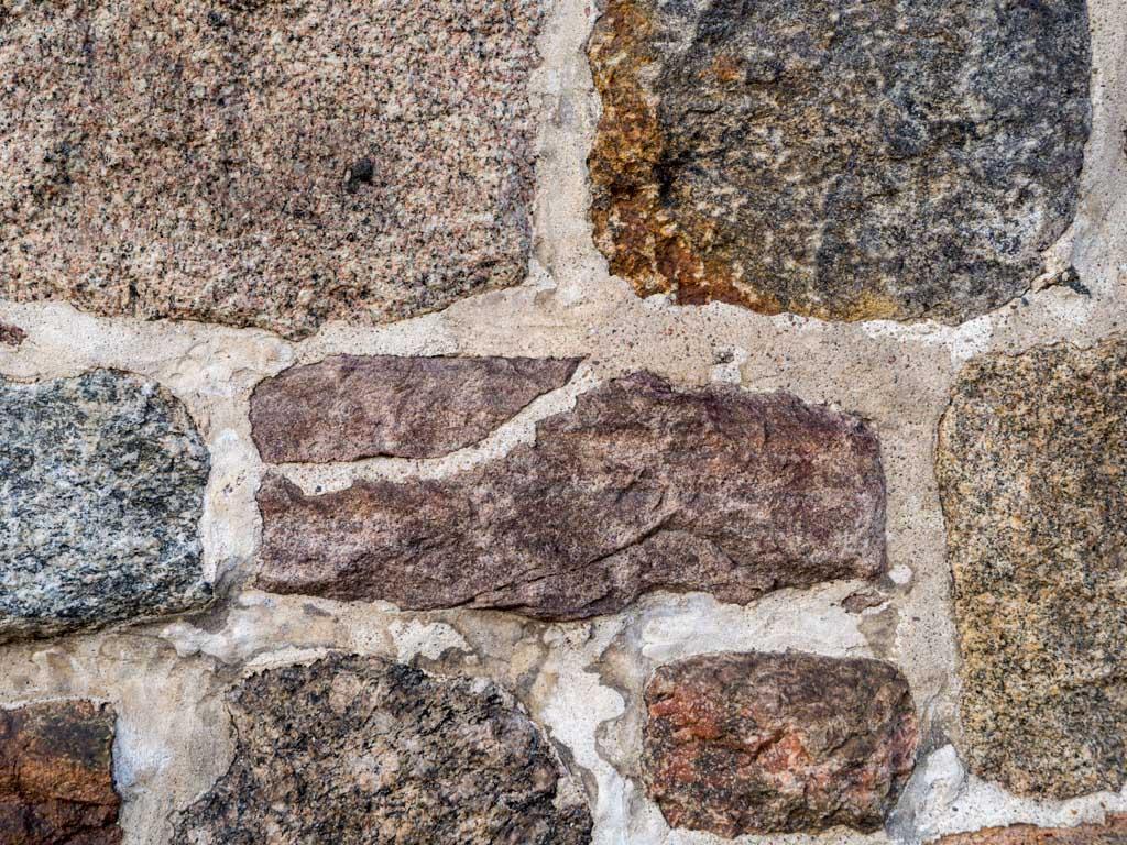 Behauener Feldstein im Mauerwerk mit verwendetem Bruchstück