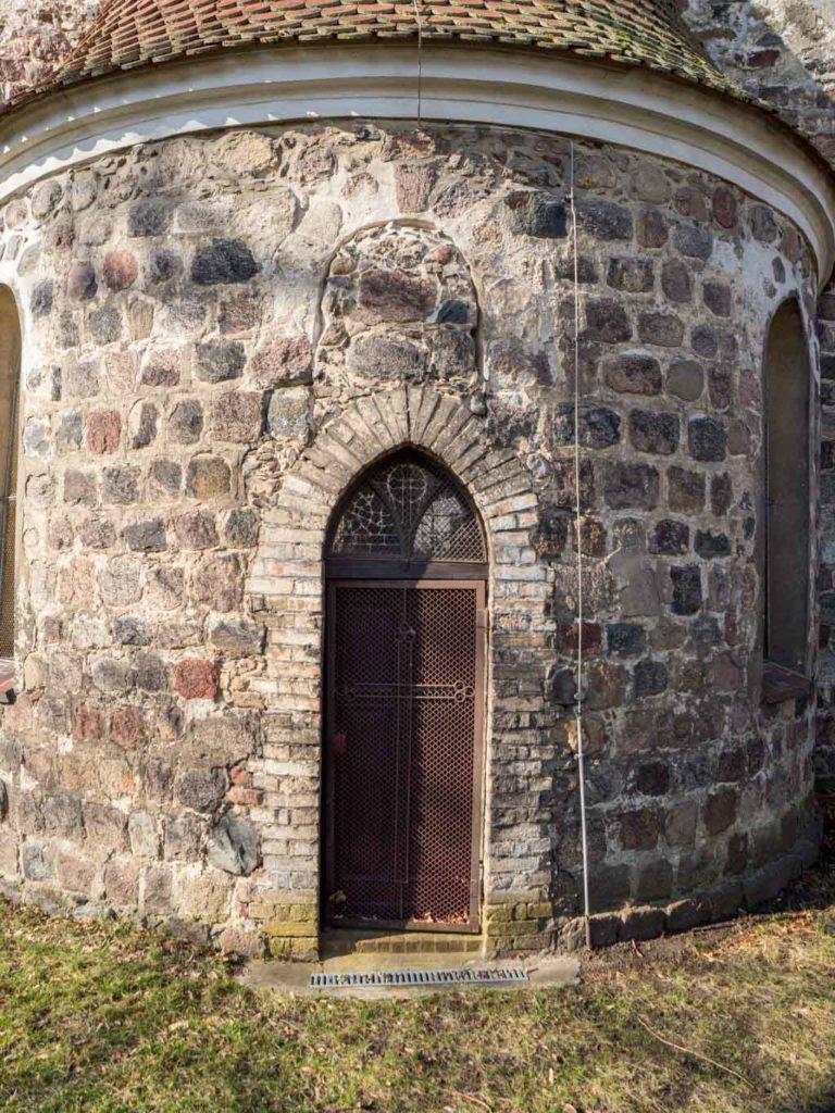 Dorfkirche Herzfelde Im 19. Jh. errichtete Tür in der Apsis. Oberhalb Relikte des zugesetzten romanischen Rundbogenfensters.