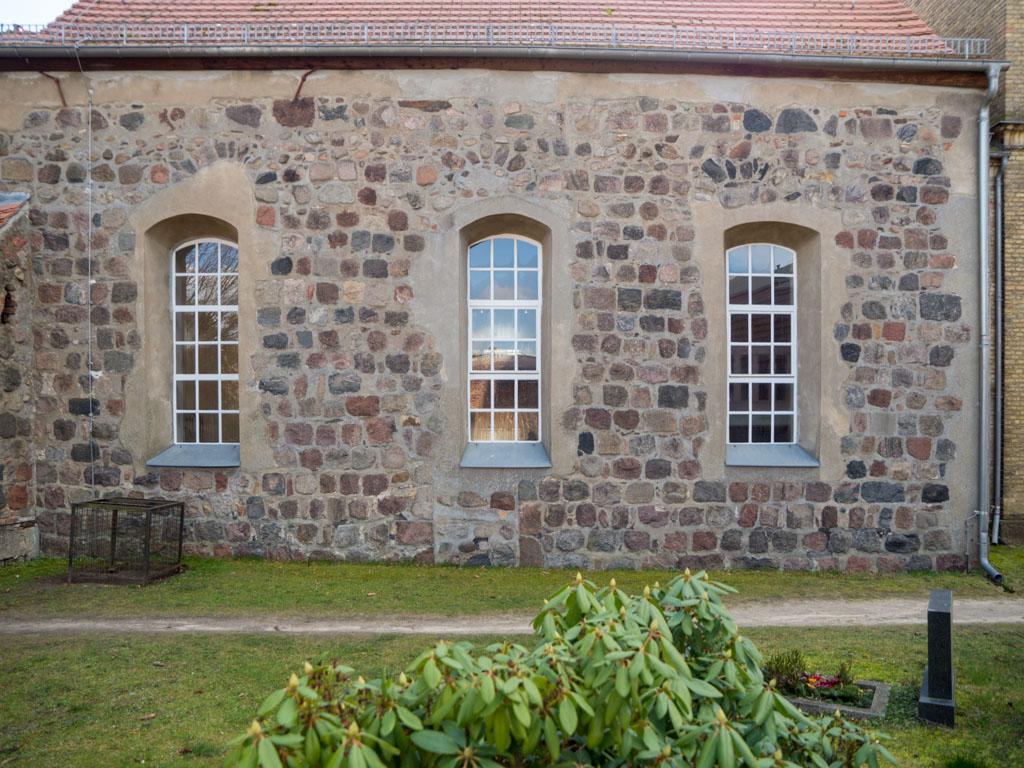 Dorfkirche Karow Nordfassade des Schiffs mit Resten dreier romanischer Fenster und eines Portals.