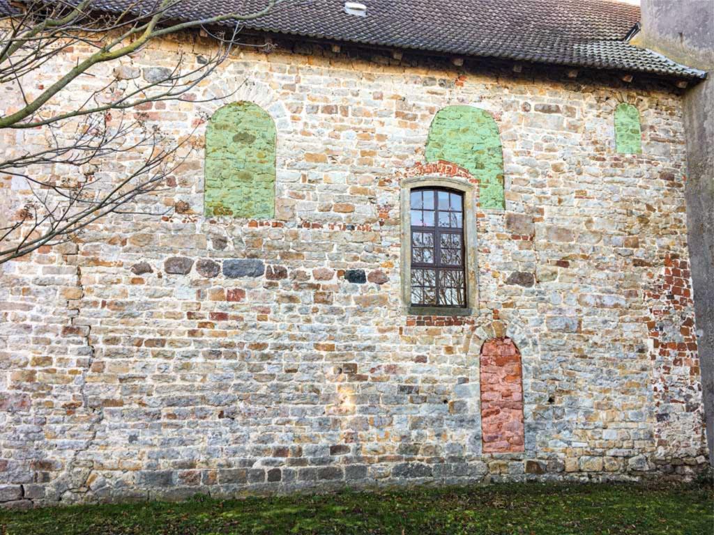 Nordseite des (einschiffigen) Chors mit zugesetzten Rundbogenfenstern und Priesterpforte.