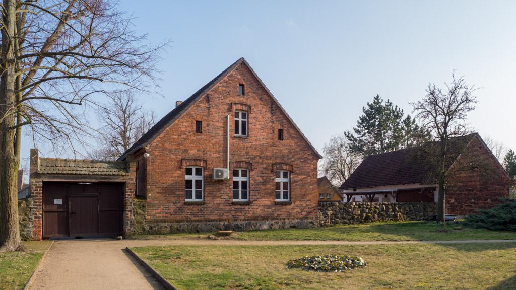 Stimmungsvolles Ensemble: Mittelalterliche Portalanlage, Backsteinhaus mit Feldsteinsockel und Feldsteinmauer zum Kirchhof.
