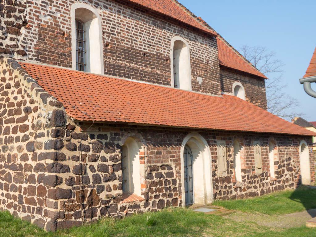 Dorfkirche Lindena. Südliches Seitenschiff mit Gemeinde- und Priesterpforte sowie drei Rundbogenfenstern und zwei Grabplatten von Kindergräbern aus dem 16. Jahrhundert.