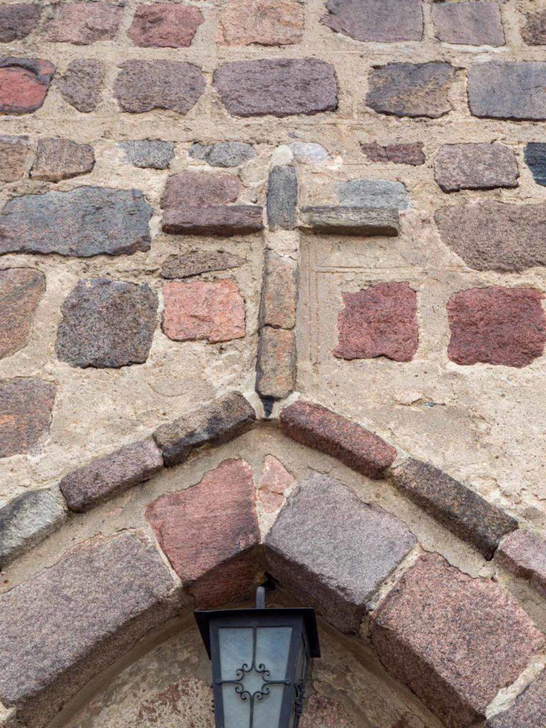 Kreuz, Überfangbogen und Putzkritzungen am Hauptportal.