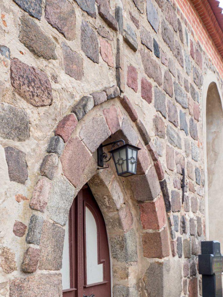 Dorfkirche Lugau, Über die Fassade herausragender Überfangbogen des Hauptportals in der Südfassade des Schiffes. Dies ist ein seltenes Schmuckelement an den brandenburgischen Feldsteinkirchen.