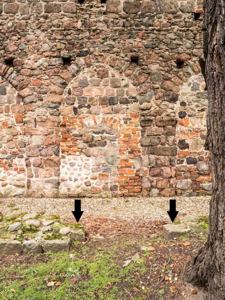 Verbliebene Relikte der ehemaligen nördlichen Gemeindepforte. Die Pfeile markieren die Sockelsteine des Gewändes.
