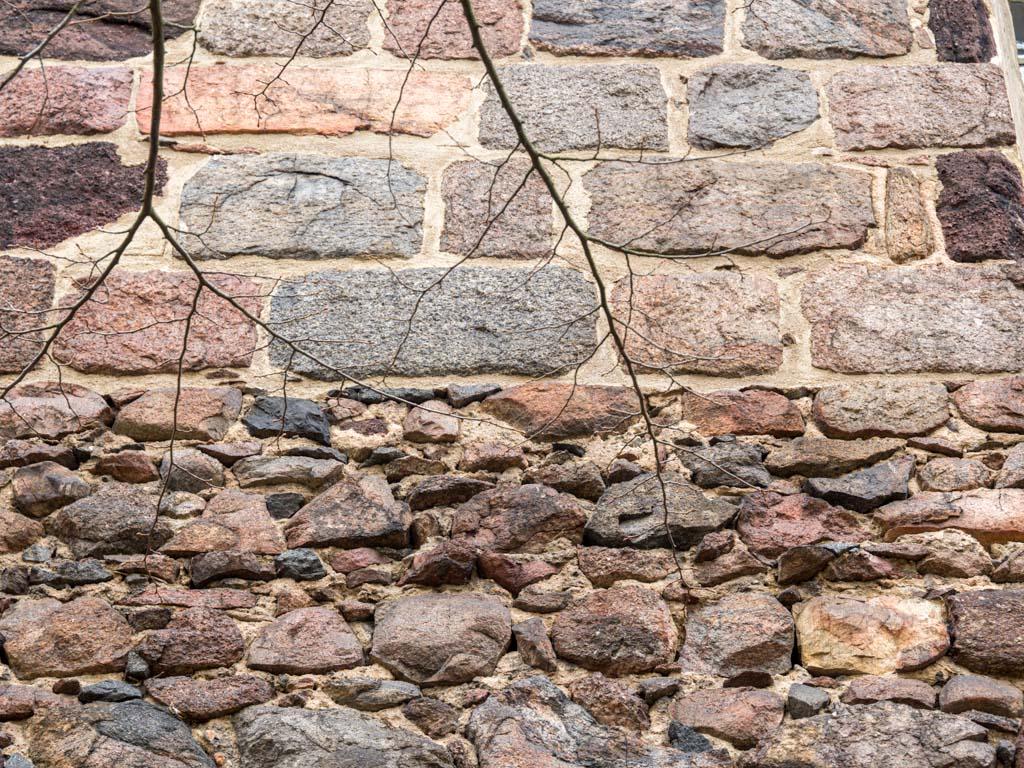 Übergang von qualitätvoll ausgeführtem Feldsteinmauerwerk (oben) zu Lagen von wenig bis unbearbeiteten kleinen Feldsteinen im Bereich des abgerissenen Seitenschiffs. Diese Partien waren verputzt und nicht sichtbar.