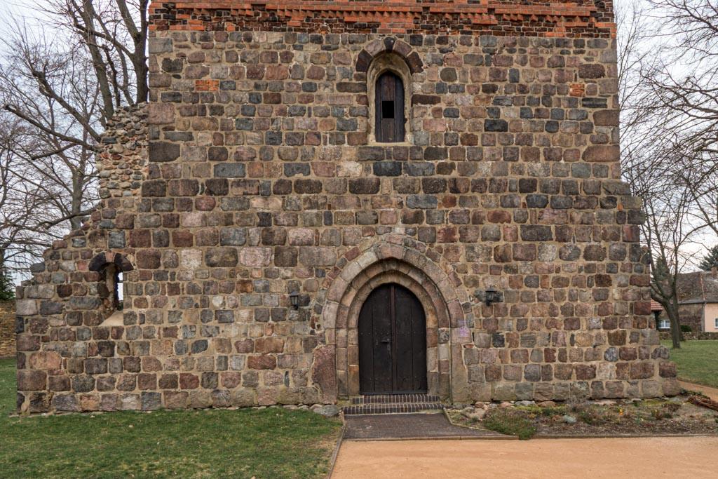 Dorfkirche Massen. Westfassade mit gedrückt spitzbogigem, dreifach abgetreppten Portal und Rundbogenfenster. Deutsches Band am Übergang zum Backstein.
