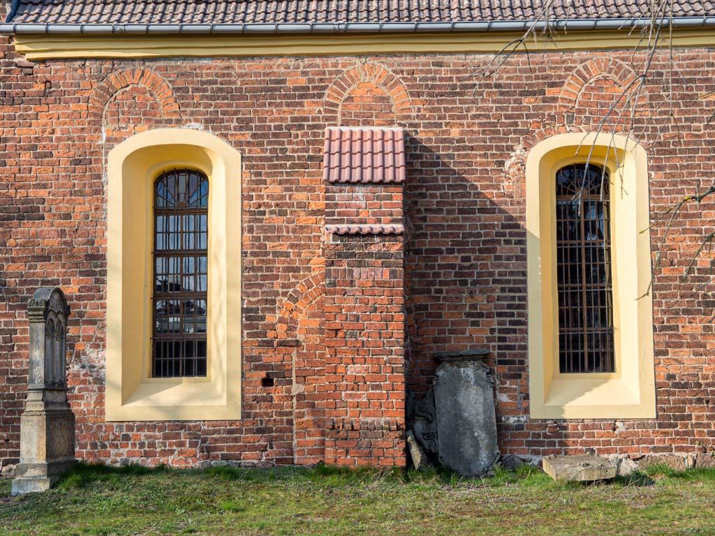 Dorfkirche Massen. Südwand des Schiffes mit spätromanischen Resten: Drei zugesetzte gedrückt spitzbogige Fenster und die ebenfalls zugesetzte Gemeindepforte. Sie wird teilweise durch die Mauerstütze verdeckt.