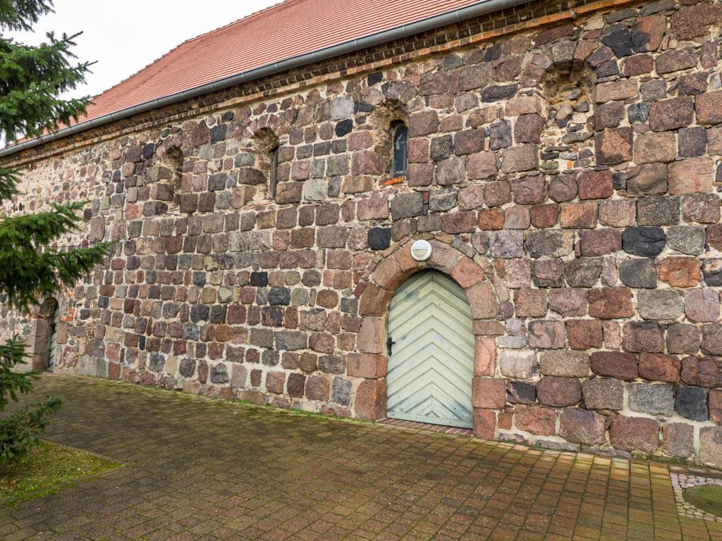Dorfkirche Linthe. Nordwand des Schiffes mit originalen Fenstern und der Gemeindepforte.