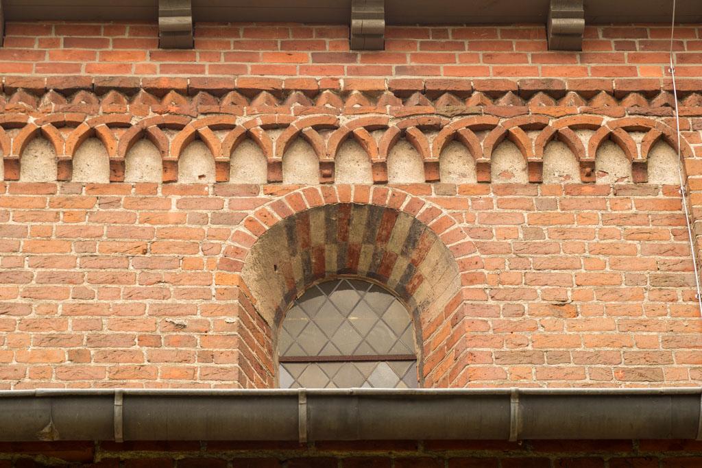 Detail des nördlichen Obergadens: Deutsches Band und Kreuzbogenfries das bemalte Gewände eines Rundbogenfensters.