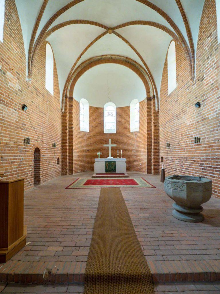 Chor mit Priesterpforte, zwei Sakramentsnischen, romanischem Taufstein und Apsis mit Altar.