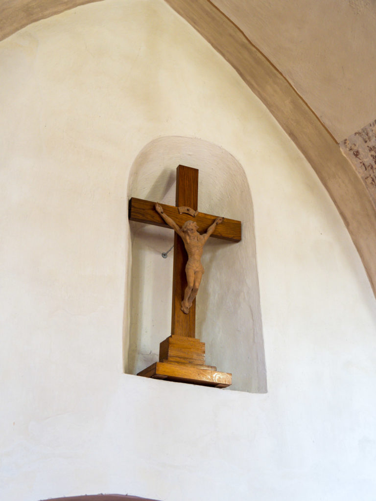 Einzig verbliebenes romanisches Fenster, zugesetzt und mit Kruzifix versehen.