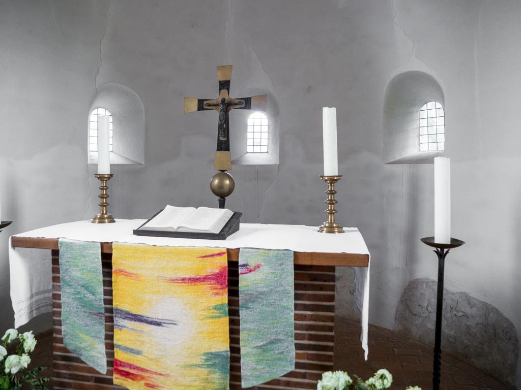 Die drei originalen Rundbogenfenster der Apsis. Mit dem Altar ergibt sich ein Bild von schlichter Anmut.