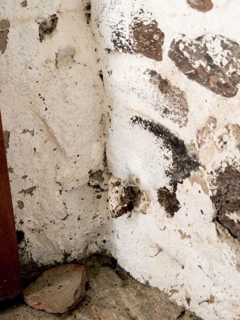 Rechte untere Scharnierbefestigung und Feldsteine des Mauerwerks