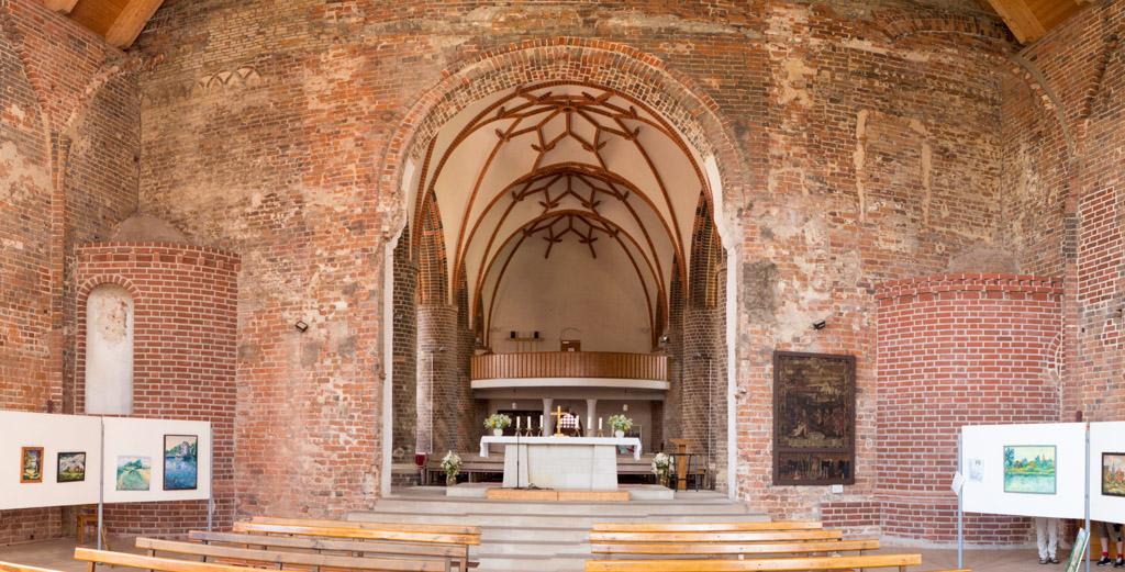 Blick entlang des heutigen Chors in Richtung Schiff auf die erhaltenen romanischen Bauteile: Rundbogiger Triumphbogen, romanische Nebenapsiden, romanisches Mauerwerk mit Kreuzbogenfries