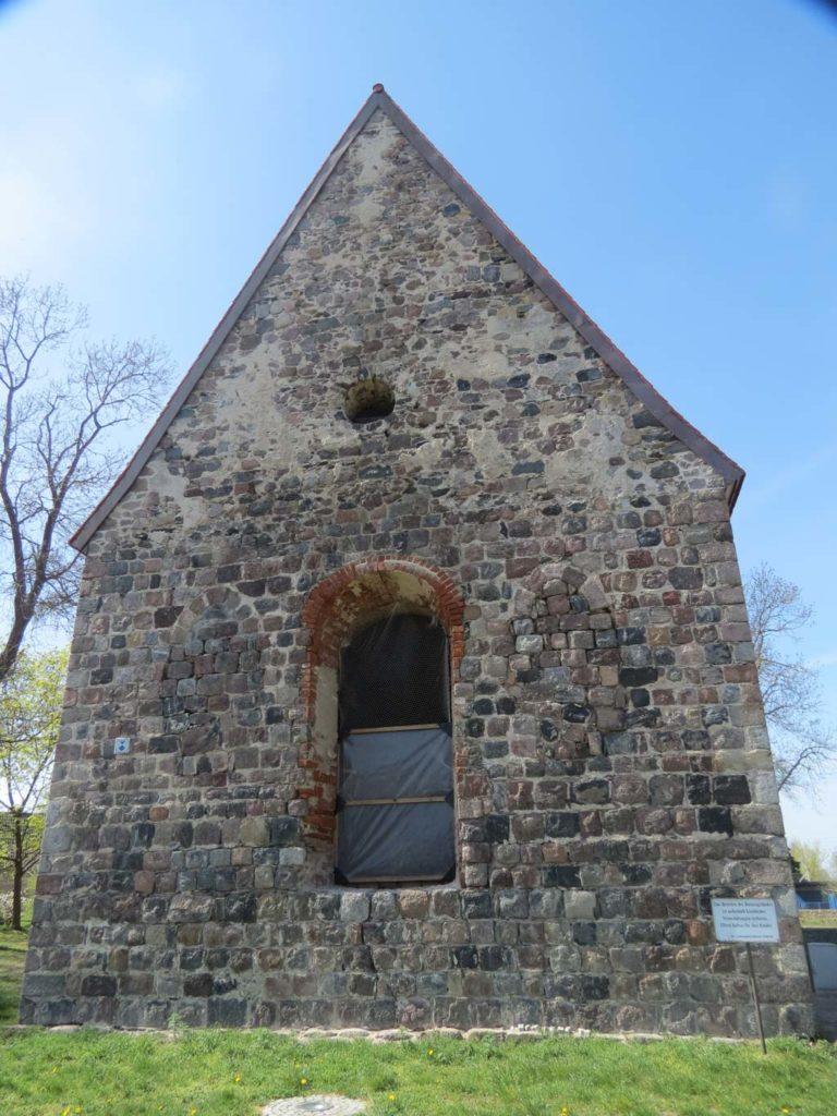 Kirche Dolgelin 2020. Ostfassade mit zwei originalen gedrückt spitzbogigen Fenstern und bis zum Giebel sauber gequadertem Feldsteinmauerwerk