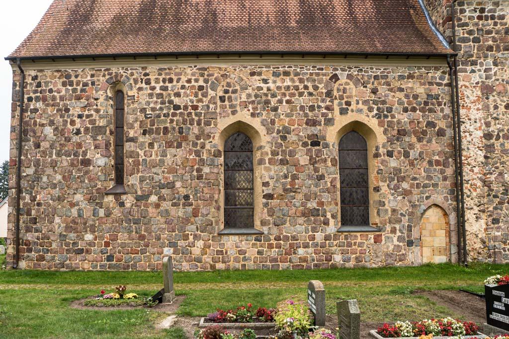 Dorfkirche Falkenhagen. Chor, Nordseite. Äquivalent zur Südseite ausgeführtes Mauerwerk und Fenster, aber ohne Sakristei. Die heute zugesetzte, spitzbogige Pristerpforte liegt kurioserweise neben einer in Relikten zu erkennenden, ebenfalls zugesetzten, rundbogigen Pforte.