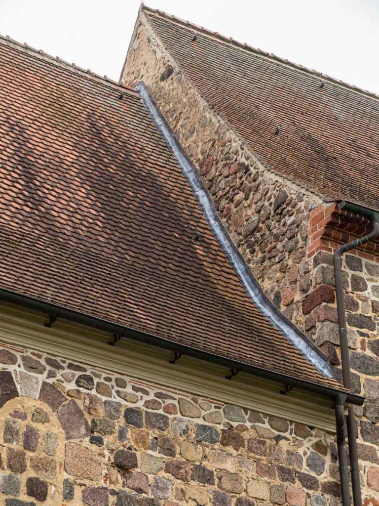 Dorfkirche Falkenhagen. Übergang von Chor zu Schiff, Nordseite. Man erkennt gestörtes Mauerwerk am Übergang zum Dach des Chors und an der Giebelwand des schiffs.