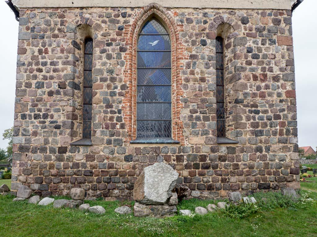 Dorfkirche Falkenhagen. Ostwand des Chors mit akkuratem Feldsteinmauerwerk und Dreifenstergruppe. Die äußeren Lanzettfenster sind original.
