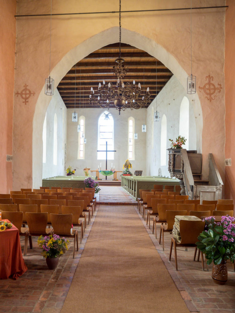 Dorfkirche Falkenhagen. Blick entlang Hauptschiff mit spitzbogigem Triumphbogen und Chor mit Altar und zwei originalen Lanzettfenstern in der Ostwand. Die südliche (rechte) Chorwand zeigt deutlich, dass der Chor schief zum Schiff verläuft.