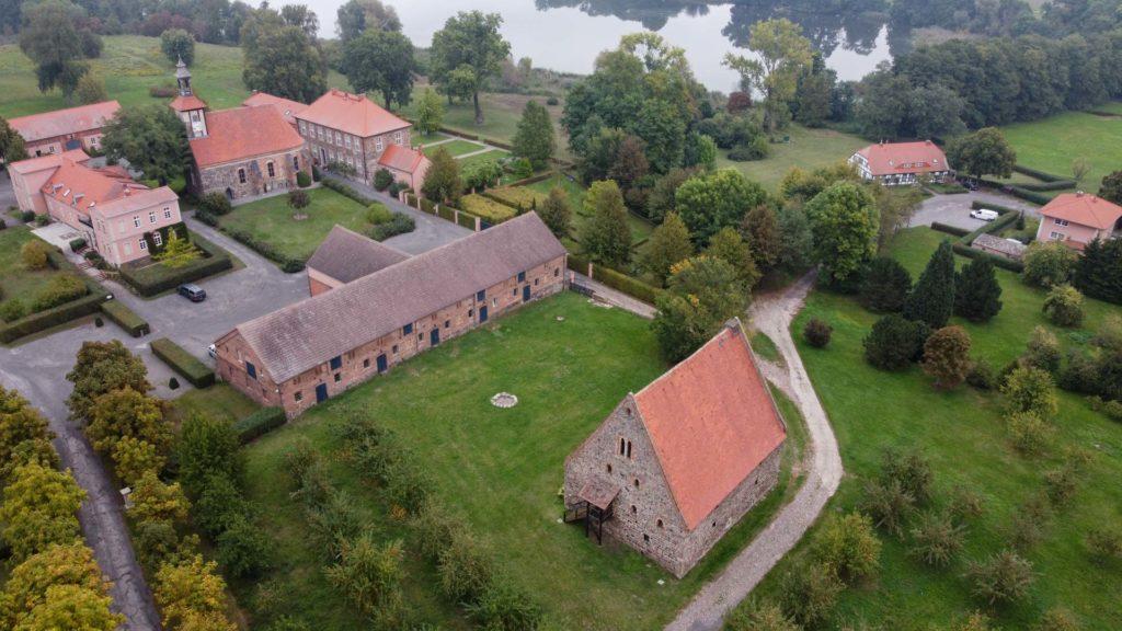 Komturei Lietzen. Im Vordergrund die Scheune, links die Ordenskirche angrenzend seeseitig das ehemalige Komtureigebäude, das heutige Herrenhaus.