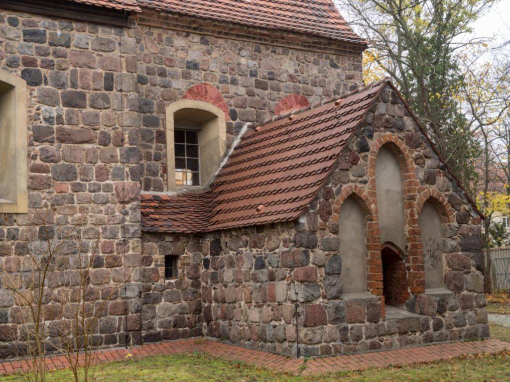 Südwand des Chors mit Sakristeianbau. Die Reste der romanischen Fenster sind farbig gekennzeichnet (A.Soujon)