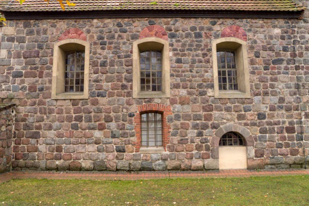 Nordwand des Schiffes. Über den Barockfenstern befinden sich die Reste der romanischen Fenster (farbig gekennzeichnet durch A. Soujon). Die Gemeindepforte dient als Fenster.