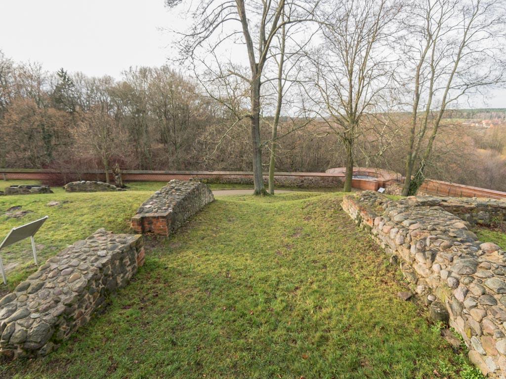 Romanisches Mauerwerk mit Portalöffnung in der westlichen Verlängerung der Kapelle. Rechts die Mauer des Westturms.
